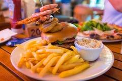 Double hamburger de viande avec la crevette rose et les fritures Photos libres de droits