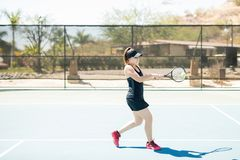 Double handed backhand shot. Professional hispanic female tennis player hitting a backhand shot with one hand on court outdoors Royalty Free Stock Photography