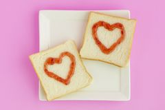 Double heart bread. Strawberry jam-painted in a heart shape on white breads Stock Photography