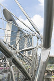 Double Helix Bridge. Engineering stainless steel structure connection of double helix bridge in Singapore with Marina Bay Sands hotel tower at the background Stock Image