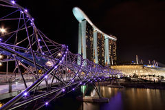 Double Helix Bridge, Singapore. Singapore's Double Helix Bridge with Marina Bay Sands and Sky Park in the background Stock Photo