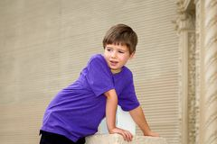 Double Jointed Young Boy with Hypermobility of the Elbow Leans F. A double jointed little boy with hypermobility of the elbow leans forward with his weight on royalty free stock image
