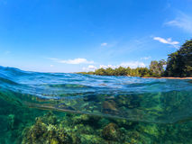 Double landscape with sea and sky. Sea panorama split photo. Undersea view with tropical island seashore. Above and below sea waterline. Snorkeling in tropical Royalty Free Stock Photography