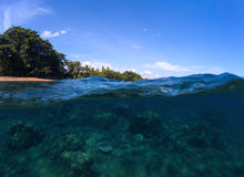 Double landscape with sea and sky. Sea panorama split photo. Undersea view of tropical island seashore. Above and below sea waterline. Blue seawater with coral Royalty Free Stock Photography