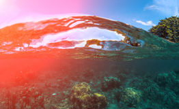 Double landscape with sea and sky. Split photo of sunny seashore. Above and below sea waterline. Tropical island nature. Seascape split view. Hot sun flare Stock Photo