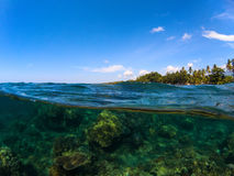 Double landscape with sea and sky. Split photo with tropical island and underwater coral reef. Royalty Free Stock Image