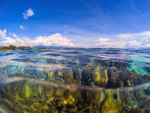 Double landscape with transparent water and sky. Transparent seawater with coral reef under water. Stock Photos