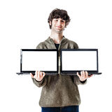 Double laptop. An handsome guy, maybe a student, in casual clothing showing two laptops with blank monitors Stock Photos
