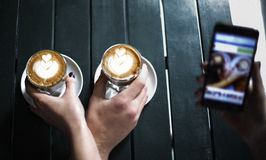 Double latte double hand. On the table royalty free stock photos