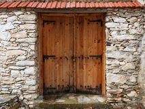Double-leaf wooden door in a stone wall Stock Images
