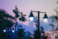 Double light bulb with steel post in evening sunset feel. Pink and purple cloudy sky, dusk  moment Stock Image