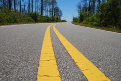 Double Lined Road. Curving through forest under blue sky Royalty Free Stock Images