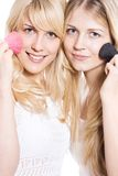 Double make up. Two young blond woman putting make up, studio white Stock Image