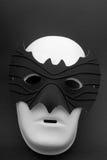 Double mask. A white mask wearing a bat-shaped mask Stock Image