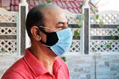 Free Double Mask Prevent Infection, Mature Indian Man Wearing Two Face Mask To Protect From New Strain Of Coronavirus Or New Wave Of Co Stock Photo - 216904600