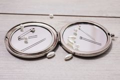 Double mirror, pins, needles and sewing items, white beads on a light wooden background. Work of seamstresses stock photography