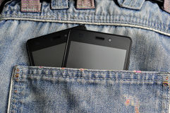 Double Mobile phone, cellphone in back pocket blue jeans Royalty Free Stock Photo