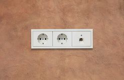 Electric sockets and network line. Light brown background. Close up view with details. stock photo