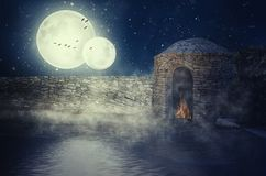 Flood inside a castle. Double moonlit night. Water of quiet lake reached very close to stone fortress wall. Little more and it will fill out flames inside of Stock Photography
