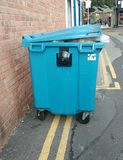 Double parked wheelie waste bin. Illegally parked blue dumpster or rubbish bin in beeston, Nottinghamshire England . These bins are for commercial use by shops Stock Photo