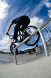 Double peg grind. Biker doing double peg grind down the hand rail over the stairs stock images