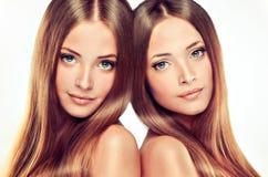 Double portrait des jumeaux magnifiques avec les cheveux sains brillants d'ONG photographie stock libre de droits