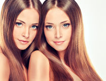 Double portrait of gorgeous twins with ong shiny healthy hair.. Double portrait of gorgeous twins. Clean, fresh skin , delicate make-up and long shiny healthy Royalty Free Stock Photo