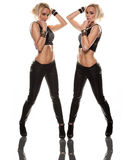 Double pose. Sexy blonde twin woman pose in black leather pants Royalty Free Stock Photo