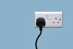 Double power socket and single plug switched on. Double electrical power socket and single plug switched on, blue background Royalty Free Stock Photography