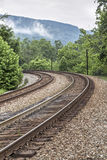 Double Railroad Tracks Curve. Around a bend and into a misty mountain landscape in the Laurel Highlands of Pennsylvania royalty free stock images