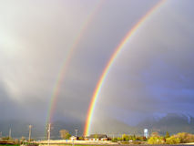 Double Rainbow. A magnificent double rainbow forms a humungous arch over a small town royalty free stock images