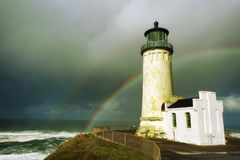 North Head Lighthouse and double rainbow. A double rainbow arches over the sea in the background of this view of North Head Lighthouse on the Washington Coast Royalty Free Stock Photo