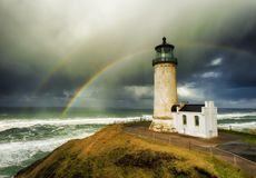 North Head Lighthouse and double rainbow. A double rainbow arches over the sea in the background of this view of North Head Lighthouse on the Washington Coast Stock Image