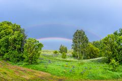 Double rainbow in the blue cloudy sky over green meadow and a forest illuminated by the sun in the country side Royalty Free Stock Images