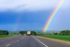 Double rainbow in the blue cloudy dramatic sky over green field and a road illuminated by the sun in the country side Royalty Free Stock Photography