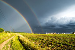 Double rainbow in the field Stock Photo