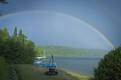 Double rainbow on a lake with beach and campfire Royalty Free Stock Image