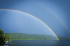 Double rainbow on a lake with boats Stock Image