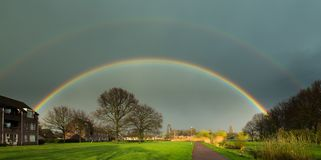 A double rainbow over Helmond Brouwhuis. After an intens rainshower this double rainbow showed up over the reential area called Brouwhuis in the city of Helmond Stock Photos