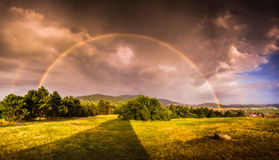 Double Rainbow over Landscape at Sunset Stock Images