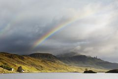 Double Rainbow over mountain. The Old Man of Storr on the Isle of Skye taken over Loch Leathann. The Storr is reflected in the calm dawn waters of the loch royalty free stock photography
