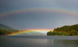 Double rainbow over a mountain lake. Stock Photos