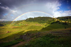 Double rainbow over the mountains. Fundatura Ponorului, Romania Stock Image