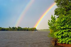 Double rainbow over the river after the rain, in the foreground green tree.  Stock Image