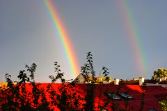 Double rainbow over roofs Royalty Free Stock Photo