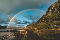 Double Rainbow over the small fishing village with blue sky and cloouds and mountains in the Lofoten Islands, Norway. royalty free stock image