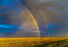 Double Rainbow. Over Wheat field as Sun is Setting Royalty Free Stock Image
