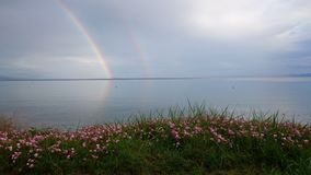Double rainbow reflecting in the sea water after a rain storm Stock Images