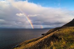 A double rainbow rises over the ocean in Iceland royalty free stock photos