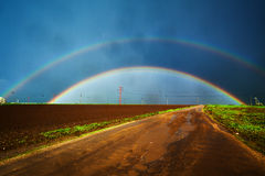 Double rainbow and road Stock Photos